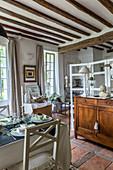 Essbereich in rustikalem Wohnraum mit Terrakottafliesenboden und Holzbalkendecke, Kommode und Raumteiler (Ausschnitt)