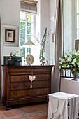 Antique chest of drawers below lattice window