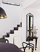 View across dining table to console table against tall wall-mounted mirror and staircase