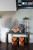 Two stools below corals and sculptures on console table