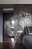 Bed against black relief wall with view into bathroom