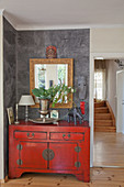 Red Oriental-style chest of drawers and ethnic accessories against grey wall