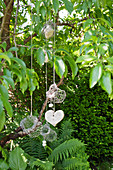 Mobile of chicken wire baskets and wooden heart hung from tree