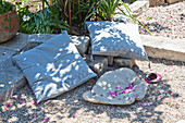 Cushions and leaf-shaped dish on gravel terrace