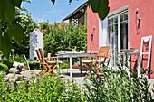 Tisch und Stühle auf der Terrasse im Garten vor einem roten Haus