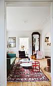 Blick ins Wohnzimmer mit Stuckdecke und buntem Stilmix