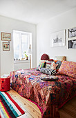 Various scatter cushions on bed with red, ethnic bedspread