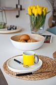 Teller mit gelber Tasse auf Korbuntersetzer auf Frühstückstisch