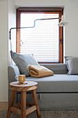 Holzhocker und graues Polstersofa mit Kissen vor Fenster