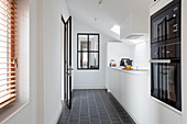 White fitted kitchen with black floor tiles and sloping ceiling