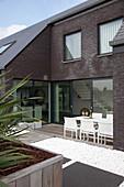 Modernes Backsteinhaus mit Essplatz auf der Dachterrasse