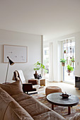 Hellbraune Ledercouch, Couchtisch, Sitzpouf und Drehstuhl im Wohnzimmer, hängende Zimmerpflanzen am Fenster