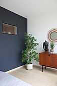 Potted tree against blue-grey accent wall, retro sideboard and sunburst mirror in bedroom