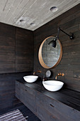 Two countertop sinks in bathroom with dark wooden walls