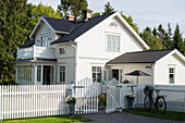 Picket fence around white Swedish house with black roof