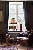 Rocking lion next to leather armchair below window