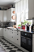 Panelled cupboards and chequered floor in white kitchen