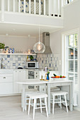 White, folding dining table and white and blue wall tiles in open-plan kitchen below gallery