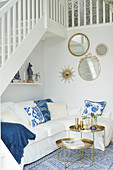 Scatter cushions on white couch and set of round tray tables below staircase with round mirrors on wall