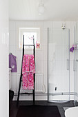 Shower stall and ladder used as towel rail in white bathroom