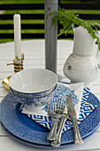 Blue and white place setting with candle and jug on garden table