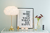 Table lamp, framed motto, vase and candlestick on sideboard with glass top