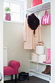 Woman's coat, hat box and pink accessories in white cloakroom