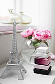 Miniatur Eiffelturm, Schachteln und Kugelvase mit Rosen auf Nachttisch