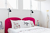 Double bed with hot-pink headboard in white bedroom