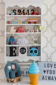 Toys on shelves mounted on wall with patterned wallpaper in child's bedroom