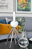 Octopus-shaped candlestick and leaves in glass vase on coffee table