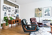 Two retro leather armchairs in front of desk below gallery of pictures on wall