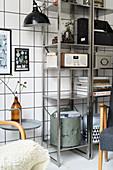 Vintage accessories and retro radio on metal shelving against tiled wall