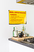 Old enamel sign on wall above kitchen accessories on wooden board