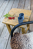 Metal candle lanterns and sprig of redcurrants on stool