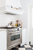 Gas cooker with extractor hood in white kitchen with black and white chequered marble floor tiles