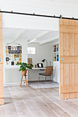 Barn-style sliding door leading into bright room with workspace