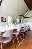 Various retro chairs with pale upholstery at long dining table