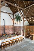 Gedeckter Tisch mit hängender Blumendeko in der Scheune