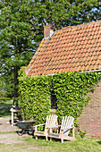 Two deckchairs against outside wall of brick house covered in ivy
