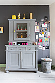 Pale grey dresser next to gallery of pictures, photos and notes on dark grey wall