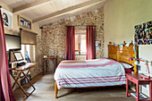 Red accents and stone wall in Mediterranean bedroom