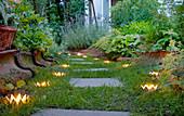 DIY-Krönchen-Windlichter aus Metalldosen am Gartenweg entlang