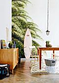 Esszimmer mit Strandfeeling durch Palmentapete und Surfbrett