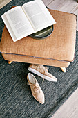 Open book on brown ottoman and beige shoes