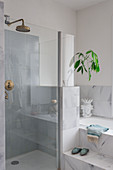 Shower with glass door next to fitted bathtub with marble tiles