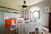 Set table and classic chairs in front of kitchen counter with bright orange base units in renovated château