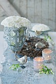 White carnations in goblet with crystal droplets, bird ornaments and tealight holders