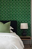 Bedroom with black, white and green colour scheme and wallpaper with graphic pattern