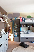 Loft bed with drawers below against mural on wall in child's bedroom
